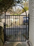 Iron  arch top gate with decorative scroll patterns by Kevin Gerry