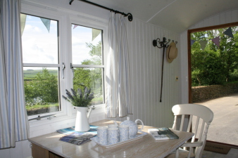 Internal view of a Duchy Shepherd's hut showing window and table.